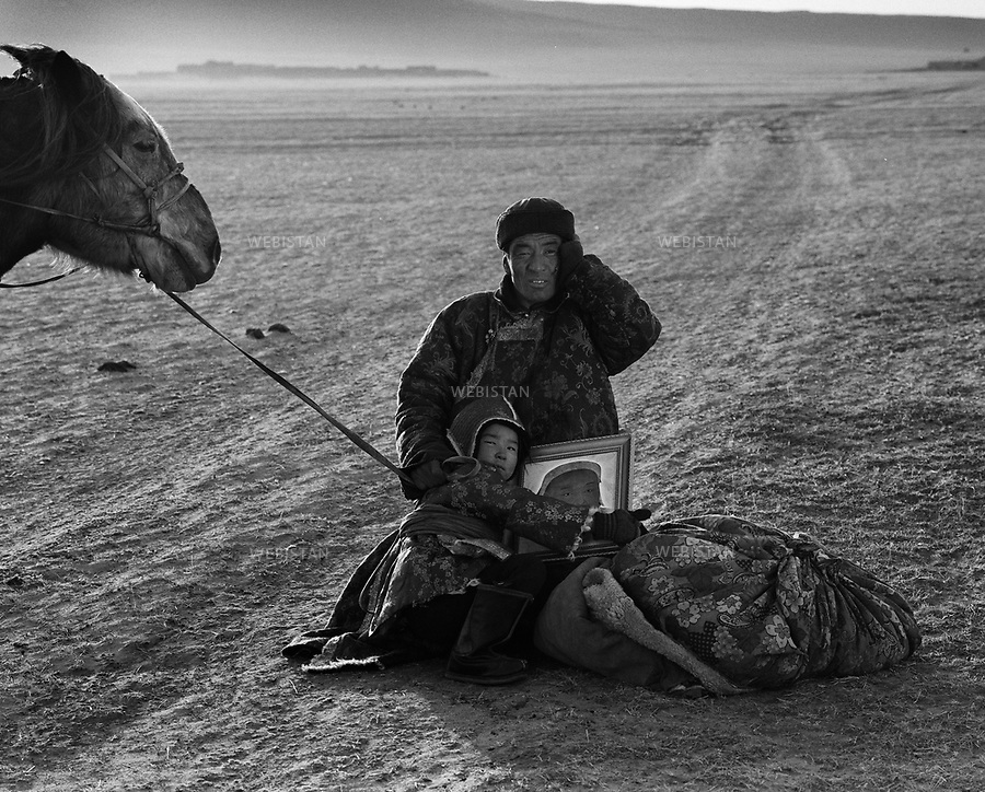 "Inner Mongolia, Xilingol Meng, East Ujimqin Qi, Baiyinhumu Sumu, Baiyinzhuo'er Gacha, April 2007.Ba - Xidurigu (age 41) and his daughter Wurihan (age 8)...On the way of sending daughter Wurihan to school in the town of Wuliyasitai, Ba-Xidurigu and daughter Wurihan is waiting for the bus next to a dried up lake. The river of Wulagai that runs through here is the ""life river"" of Xilingol Grassland. It's the biggest inland river on the Inner Mongolia Plateau, originated in the west part of Mont. Se'erjibaogada in Daxing'anling, joined by 15 smaller rivers, travels 320 kilometer and covers an area of 28,000 square kilometer. The drainage area of  Wulagai river includes Hesigelawu, Halagaitu and Wulagai these three pastureland, as well as Huretuzhuo'er, Wulagai, Wenggen, Daotezhuo'er, Baolige and Wentgu these six sumus, irrigating 23.43% of grassland in East Ujimqin Qi..At the end of the 1970's, reservoirs were built on Wulagai River for fishery. After 1988, East Ujimqin grassland suffered from draughts year after year, the original rivers and lakes were drying up by the day. Under the influence of natural disasters, the Wulagai River gradually slimed down, until 2007, it completely ran out of water. The big river had no water, the small ones dried up as well, Wulagai river's each branch rivers were all out of water. These exhausted rivers and lakes are, Gaorihan river, Jigasutai River, Yinjigan River, Balaga'er River, Wuyoutu River, Jiruanbaola river, Chongyin River, Seye'erji river, Wunugan River, Xilin river, Chagan Lake, Tege Lake, Habutagai Lake, Yihe Lake, Huyin Lake and Daote Lake."