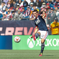 New England Revolution midfielder Andy Dorman (12) passes the ball.  In a Major League Soccer (MLS) match, the New England Revolution (blue/white) tied Vancouver Whitecaps FC (white), 0-0, at Gillette Stadium on March 22, 2014.