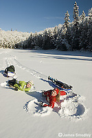 Happy girls making snow angels while ice fishing
