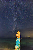 A woman looking at the Milky Way on the beach