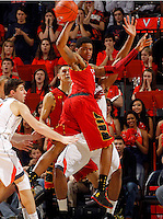 Maryland guard Nick Faust (5) passes the ball behind him over Virginia guard Joe Harris (12) during the game Sunday in Charlottesville, VA. Virginia defeated Maryland in overtime 61-58.Photo/Andrew Shurtleff