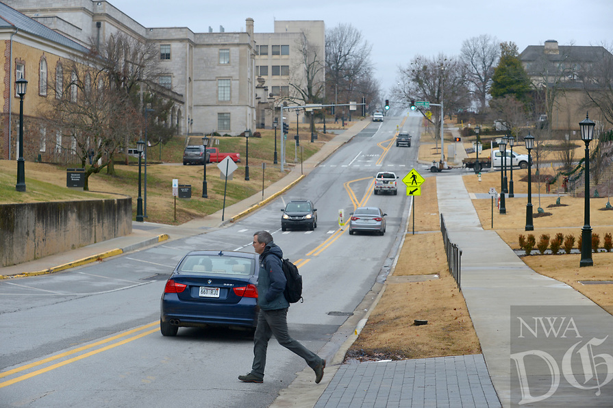 NWA Democrat-Gazette/ANDY SHUPE<br /> A pedestrian crosses Maple Street Thursday, Jan. 3, 2018, on the University of Arkansas campus in Fayetteville. The city of Fayetteville and University of Arkansas are planning to install a two-way bicycle track on Maple Street from the Razorback Greenway near Gregg Avenue to Garland Avenue. Estimated cost on the project is $4 million.