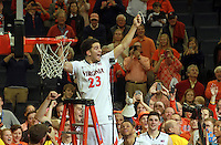 Virginia guard London Perrantes (23) cuts his piece of net to celebrate winning the ACC title after defeating Syracuse 75-56 Saturday March 1, 2014 during an NCAA basketball game in Charlottesville, VA.