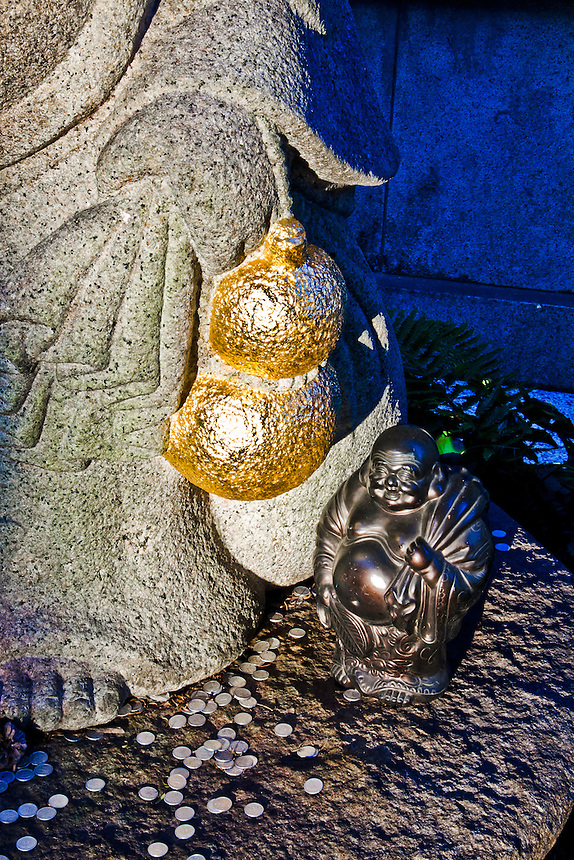 Big and little Buddha`s with coin offerings at Zenyomitsuji Buddhist temple.