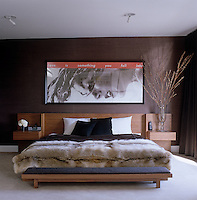 A Barbara Kruger print hangs above the walnut bed with integrated side tables and headboard