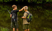 A Boy Scout jokes with his friend, who shaved his head while attending Boy Scout resident camp in summer 2010 at Camp Raven Knob. Camp Raven Knob Scout Reservation, one of the largest Boy Scout camps in the United States, is located within Boy Scouts of America's Old Hickory Council in Mt. Airy, North Carolina. Troops from across the US attend the camp's one-week residential boys' summer programs, which offer instruction on more than 40 merit badges, adventure programs and new Scout orientation.