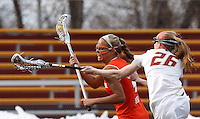 Syracuse University midfielder Erica Bodt (4) on the attack as Boston College defender Claire Blohm (26) defends.  Syracuse University (orange) defeated Boston College (white), 17-12, on the Newton Campus Lacrosse Field at Boston College, on March 27, 2013.