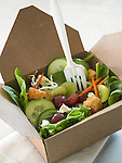 A green salad with cucumber, grapes, croutons, and feta in a paper to-go box with plastic fork