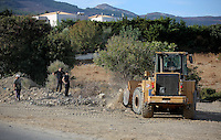Pictured: A digger loads soil from the second site to be transported to the farmhouse so that specialist officers search through it in Kos, Greece. Monday 10 October 2016<br />