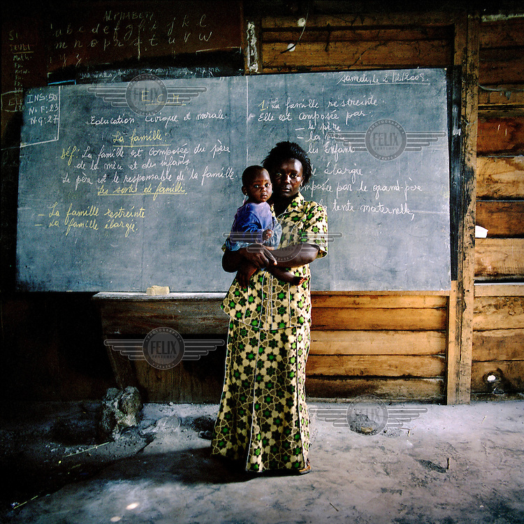 14 year old Masengi, and her baby born as a result of her rape, standing in the school she  sometimes attends in the Heal Africa Hospital.  ©Robin Hammond/PANOS/Felix Features