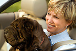Mature woman with dog in car, close-up