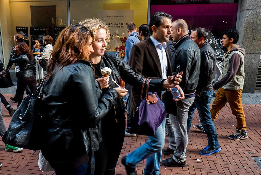 Nederland, Amsterdam, 21 sept 2013<br /> Nieuwendijk op zaterdagmiddag. Twee meiden die net een ijsje hebben gekocht maken een foto van zichzelf met smartphone.<br /> Shopping street. Two girls making pictures of themselves after buying an icecream.<br />  Foto(c): Michiel Wijnbergh