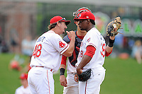 Pitching coach Paul Abbott (48) of the Greenville Drive talks with pitcher German Taveras in a game against the Asheville Tourists on Sunday, July 20, 2014, at Fluor Field at the West End in Greenville, South Carolina. Asheville won game two of a doubleheader, 3-2. (Tom Priddy/Four Seam Images)