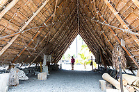 A visitor walks through a traditional thatched Hawaiian hale at Pu'uhonua o Honaunau, or City of Refuge, Big Island of Hawai'i.
