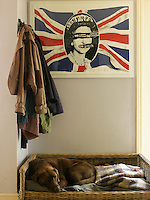 A 1977 Sex Pistols promotional poster hangs above the dog's bed in the hallway