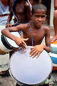 Itaparica Island, Bahia State, Brazil. Boy playing a drum in a street procession.