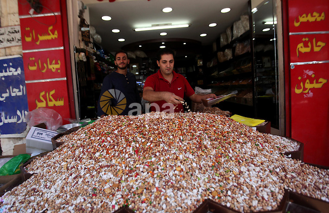 A Palestinian vendor sells nuts at a market ahead of the Eid al-Adha festival in the West Bank city of Nablus on Sept. 11, 2016. Photo by Nedal Eshtayah