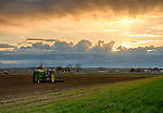 Idaho, Western, Parma/Oregon, Eastern, Nyssa. Spring sunrise south of Odyessa,  with a John Deere tractor parked in a freshly plowed field.