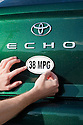 Close up of man attaching a 38 miles per gallon fuel efficiency bumper sticker installed on Toyota Echo car. Sticker from MPG Stickers (mpgstickers.com), a grassroots, nonprofit campaign which aims to accelerate the adoption of fuel efficient vehicles in the United States. California, USA. Property released from mpgstickers.com.