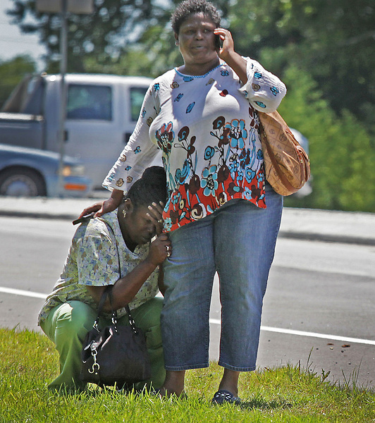 Chuck Beckley/Sun Journal    Rhonda Hill fell to her knees and hugged the leg of her friend Katrina Nelson, Monday afternoon upon arriving home and seeing firemen puting out the fire at her house. Rhonda, her husband, daughter and two grandchildren lived in the wood frame home on 55 West.