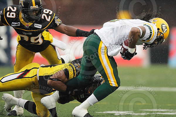 August 8, 2009; Hamilton, ON, CAN; Hamilton Tiger-Cats linebacker Markeith Knowlton (25) and defensive back Lawrence Gordon (29) tackle Edmonton Eskimos slotback Fred Stamps (2). CFL football: Edmonton Eskimos vs. Hamilton Tiger-Cats at Ivor Wynne Stadium. The Tiger-Cats defeated the Eskimos 28-21. Mandatory Credit: Ron Scheffler. Copyright (c) 2009 Ron Scheffler.