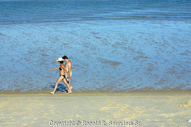 Vacationing man and woman stroll along beach at San Felipe