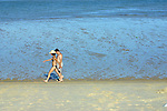 Vacationing man and woman stroll along beach at San Felipe