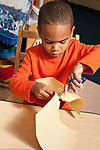 Education preschool 3-4 year olds boy cutting paper with scissors