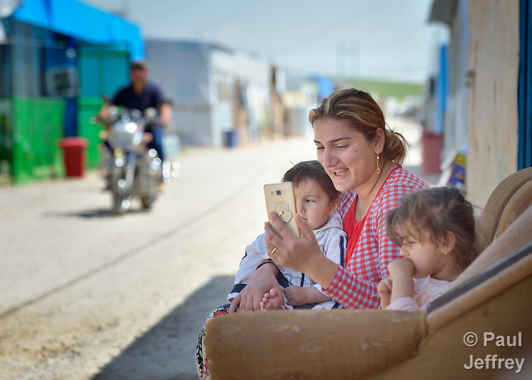Adra Samar uses Skype to talk to a relative in Baghdad as she sits in a camp for internally displaced families in Ankawa, near Erbil, Iraq, on April 8, 2016. Residents of the camp, mostly Christians, were displaced from Mosul, Qaraqosh and other communities in Iraq when ISIS swept through the area in 2014.