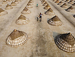 Workers create beautiful patterns as they begin the long process of making rice.  Under the boiling sun, they spread the harvested rice crop across fields to dry - routinely turning it over.<br /> <br /> Once it is dry, it is collected, packed into dome-like shapes and covered with a triangular bamboo basket.  Amateur photographer Hedayet Sarker pictured the process in Kalishima village, near his home in Brahmanbaria, Bangladesh.  SEE OUR COPY FOR DETAILS.<br /> <br /> Please byline: Hedayet Sarker/Solent News<br /> <br /> © Hedayet Sarker/Solent News & Photo Agency<br /> UK +44 (0) 2380 458800