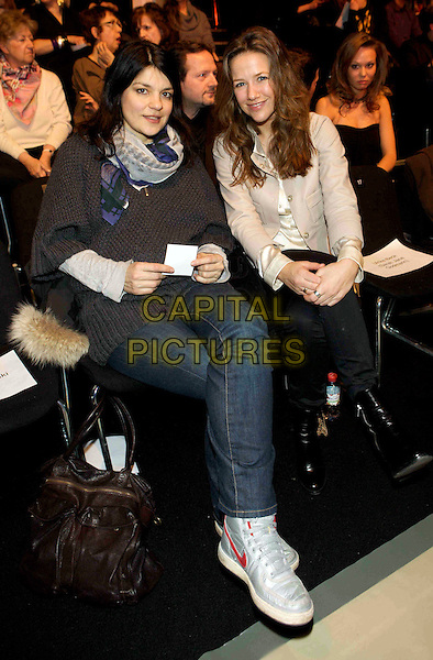 JASMIN TABATABAI & ALEXANDRA NELDEL.LALA Berlin Fashion Show, Bebelplatz, Berlin, Germany..January 29th, 2009.full length sitting jeans denim brown jumper top beige jacket.CAP/PPG/JH.©Jens Hartmann/People Picture/Capital Pictures