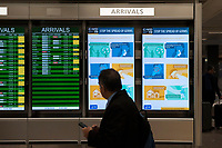 A man passes a flight board and a healthcare information sign at the international terminal at Dulles International Airport in Dulles, Va., Monday, March16, 2020. Some people are taking the precaution of wearing face masks as they arrive to be greeted by family and or friends. Credit: Rod Lamkey / CNP/AdMedia