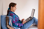 College student sitting on bed using a laptop in dorm room before classes early morning