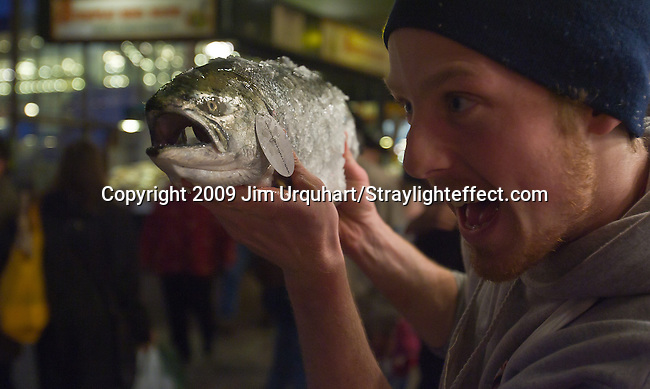 Jim Urquhart/Straylighteffect.com Fish monger Ryan Rector entertains shoppers with a fish at the Pike Place Fish Market at the Pike Place Market in Seattle, Washington. 12/22/2009 - Jim Urquhart/Straylighteffect.com