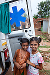 21 May 2013, Mandiganal Village, Karnartaka, India:  Kowshalyya (9) and Rajeshwari (9) stand at the mobile health clinic ambulance at Mandiganal Village. The World Bank is financing the Karnataka Health Systems Project that is bringing mobile health clinics to remote villages in Karnataka and covers the cost of an ambulance, a doctor, pharmacist, two nurses, a cleaner and a driver. Villagers have the opportunity to see a doctor once a week for basic services and will be referred to Primary Health Care centres for larger issues Picture by Graham Crouch/World Bank