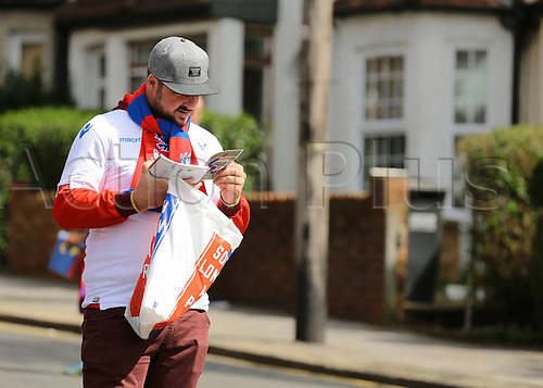 09.04.2016. Selhurst Park, London, England. Barclays Premier League. Crystal Palace versus Norwich. A Crystal Palace fan checks out the match day program