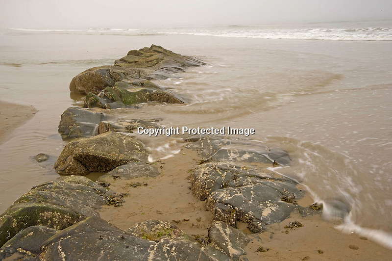 Beach Rocks and Incoming Tide on a Foggy Beach on the Coast of Maine