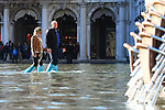Tourist walk with boots on flooded streets at St Mark's square during an acqua alta (high-water). The Acqua Alta, a convergence of high tides and a strong sirocco, reached 125 centimetres in Venice, on November 20, 2013.  <br /> <br /> &copy; Pierre Teyssot