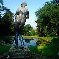A curvaceous statue stands amongst several other classically inspired figures overlooking a pond at Rousham Park