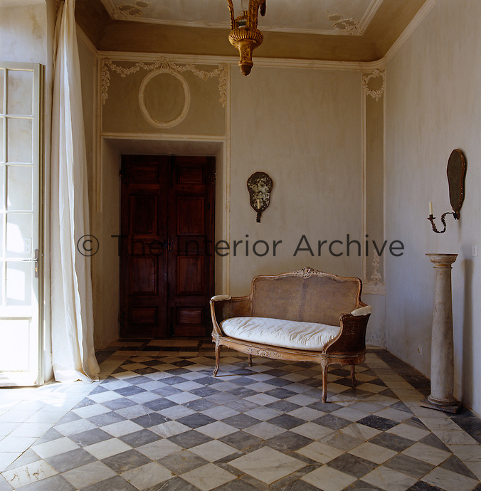 A small cane sofa stands on the tiled marble floor of this elegant entrance hall