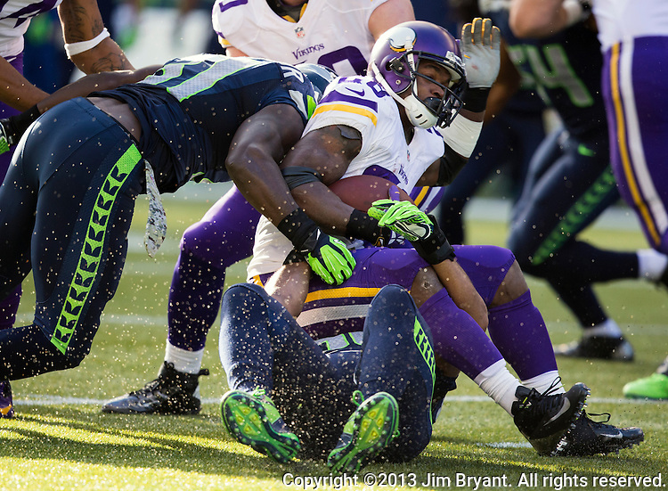 Minnesota Vikings running back Adrian Peterson is gang tackled by Seattle Seahawks Kam Chancellor (31) and Earl Thomas (29)  at CenturyLink Field in Seattle, Washington on  November 17, 2013.  The Seahawks beat the Vikings 41-20.  ©2013.  Jim Bryant. All Rights Reserved.