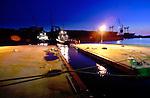 ROTTERDAM - In het Botlekgebied bereidt slepersbedrijf Smit Internationale voor zonsopgang zich voor voor het transport van het eerste drijvende tunnelelement van de Calandtunnel. De ruim honderd meter lange betonnen bak die met hulp van ballasttanks nauwelijk boven water uitsteekt, wordt vanaf de scheepswerf Verolme naar de 7e Petroleumhavenin gesleept om later te worden afgezonken. De in opdracht van Rijkswaterstaat door Ballast Nedam Beton en Waterbouw, Strukton Betonbouw, Van Oord ACZ en Ballast Nedam Baggeren gebouwde tunnel gaat 350 miljoen gulden kosten en wordt bijna anderhalve kilometer lang. Bij het afzinken zullen duikers de elementen onder begeleiden. De tunnel is onderdeel van de snelweg A15 van Rotterdam naar de Maasvlakte. COPYRIGHT TON BORSBOOM