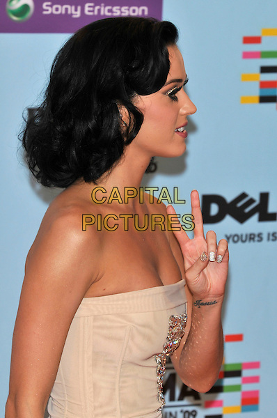 KATY PERRY .during the MTV Europe Music Awards 2009 at the O2 World Arena in Berlin, Germany, November 5th 2009..Winners photocall EMA EMAs half length v hand gesture tattoo wrist side profile strapless beige .CAP/PL.©Phil Loftus/Capital Pictures