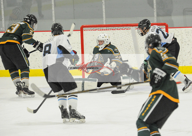 Chugiak's Zach Krajnik, at right, prepares to put a rebound past Colony goalie Alex Gamez in the final moments of the Mustangs' 3-2 win. at the McDonald Center in Eagle River Tuesday night. Photo for the Star by Michael Dinneen
