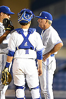 Dunedin Blue Jays pitching coach Darold Knowles (32) talks with pitcher pitcher Efrain Nieves (46) as catcher Derrick Chung (1) listens in during a game against the Daytona Cubs on April 14, 2014 at Florida Auto Exchange Stadium in Dunedin, Florida.  Dunedin defeated Daytona 1-0  (Mike Janes/Four Seam Images)