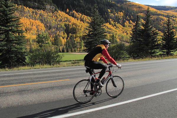 Older man riding along side the Vail Golf Course, Vail, Colorado.