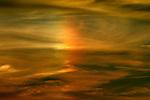 A flock of birds fly across a sun ghost or fire rainbow.