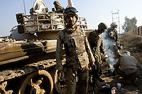 Iraqi tankers from the 1st company, 1st armour battalion of the 1st mechanized Iraqi Army Brigade prepare their tea seeking ccover in back of their tank   while conducting  patrols, check points and observation posts on code name route Michigan, the main road of Ramadi in the week during the national election on TUE Dec 13 2005 in Ramadi, Iraq. 1st company is part of the first armor battalion of the New Iraqi Army. it has started its training in January 2005. after 50 days their 35 russian and chinese built T 55 tanks begun conducting operations under the guidance of a US military adivisor team. in April 2005 they patrolled in the Abu Ghraib area concluding their first significant mission. While these old tanks are rolling on the ramadi streets more modern T72s are getting ready to become fully operational in Taji, their main base. the Iraqi army wanted to show their power in ramadi during the Dec 15 elections displaying their new armour company. but like all the other Iraqi forces they are not going to secure the polling sites, staying in the rear with the rest of the iraqi and coalition forces. T 55s are very old tanks. production begun in the late 50s to the late 70s. athough obsolete many countries still use the T55 as their main heavy armoured combat vehicle. slow, heavvy and with very little room for the crew it suffers from many mechanical problems constantly challenging the iraqi mechanics and engineers.