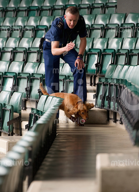 A policeman checks the seats on Court 1 with his sniffer dog Preparation for The Wimbledon Championships 2010 The All England Lawn Tennis & Croquet Club  Saturday Pre Championships Saturday 18/06/2010