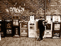 A boy looks though a free magazine next to newspaper machines in downtown Asheville, NC, sepia, iPhone photo from the archive at bcpix.com. (Photo by Brian Cleary/www.bcpix.com)
